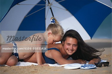 Girl (4-5) kissing mother on back at beach Stock Photo - Premium Royalty-Free, Image code: 6106-05531416