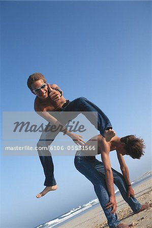 Boy (!2-13) leapfrogging over friend (!0-11) on beach, low angle view Stock Photo - Premium Royalty-Free, Image code: 6106-05531566