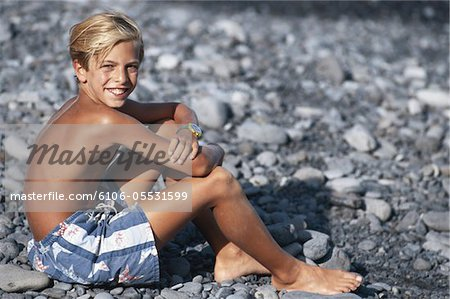 Boy (10-11) sitting on pebble beach, looking over shoulder, smiling Stock Photo - Premium Royalty-Free, Image code: 6106-05531599