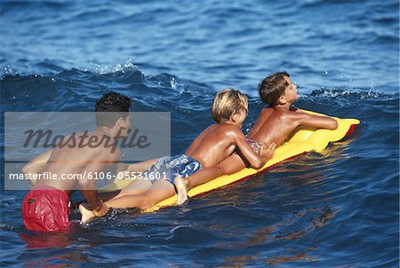 Man pushing boys (8-11) on airbed in sea Stock Photo - Premium Royalty-Free, Image code: 6106-05531601