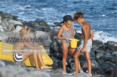Children (6-11) on beach with bucket and airbed Stock Photo - Premium Royalty-Free, Image code: 6106-05531609