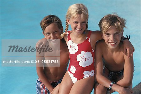 Girl (4-7) sitting along with boys (8-13) by poolside, smiling, elevated view Stock Photo - Premium Royalty-Free, Image code: 6106-05531753