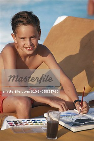 Boy (8-11) painting with water colours by poolside Stock Photo - Premium Royalty-Free, Image code: 6106-05531760