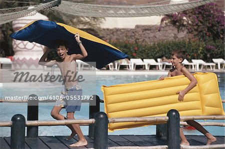Two boys (6-13) carrying airbed, walking on footbridge in swimming pool Stock Photo - Premium Royalty-Free, Image code: 6106-05531792