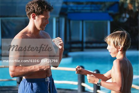 Father and boy (10-13) boxing by poolside Stock Photo - Premium Royalty-Free, Image code: 6106-05531798