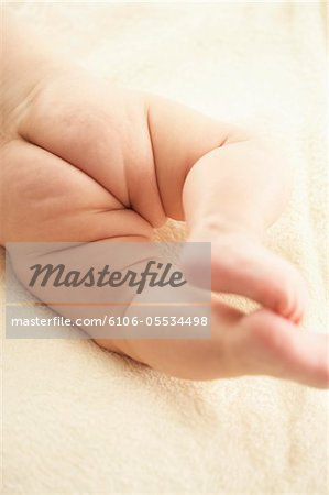 Baby girl (3-6 months) lying on stomach, low section, close-up Stock Photo - Premium Royalty-Free, Image code: 6106-05534498