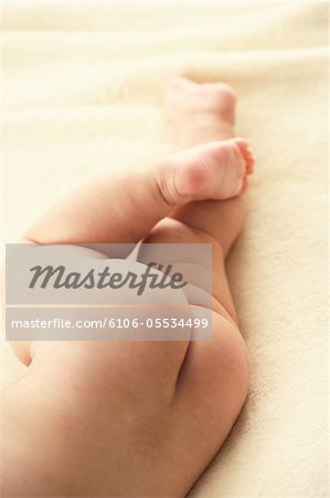 Baby girl (3-6 months) lying on side, low section, close-up Stock Photo - Premium Royalty-Free, Image code: 6106-05534499