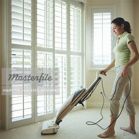 Woman cleaning room with vacuum Stock Photo - Premium Royalty-Free, Image code: 6106-05534863