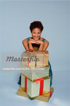 Young woman behind stack of gift boxes smiling, portrait Stock Photo - Premium Royalty-Free, Image code: 6106-05537255
