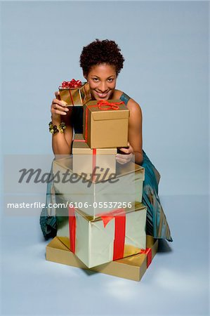 Young woman behind stack of gift boxes smiling, portrait Stock Photo - Premium Royalty-Free, Image code: 6106-05537256