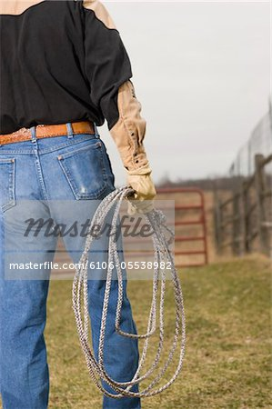 Cowboy holding lasso rope, mid section, rear view Stock Photo - Premium Royalty-Free, Image code: 6106-05538982