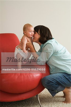 Young mother hugging baby girl (3-6 months) on chair Stock Photo - Premium Royalty-Free, Image code: 6106-05539000