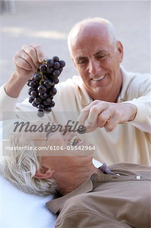 Mature man feeding grapes to woman, laughing Stock Photo - Premium Royalty-Free, Image code: 6106-05542964