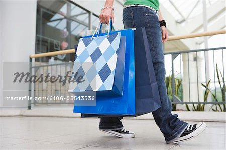 Teenage girl (15-17) in shopping centre carrying bags, low section Stock Photo - Premium Royalty-Free, Image code: 6106-05543536