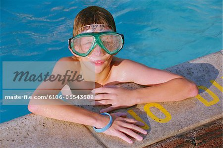 Boy (11-13) with goggles leaning on edge of pool, portrait Stock Photo - Premium Royalty-Free, Image code: 6106-05543582