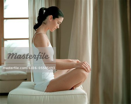 Young woman sitting cross-legged on stool, meditating, eyes closed Stock Photo - Premium Royalty-Free, Image code: 6106-05545493