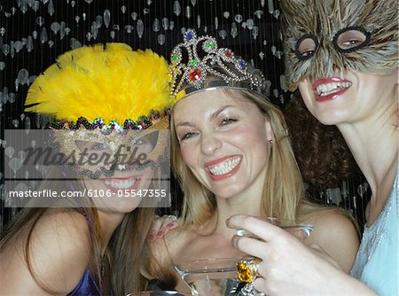 Two women wearing masks and tiara, holding drinks, smiling, portrait Stock Photo - Premium Royalty-Free, Image code: 6106-05547355