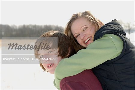 Teenage boy (14-16) giving teenage girl (14-16) piggyback in snow Stock Photo - Premium Royalty-Free, Image code: 6106-05547626