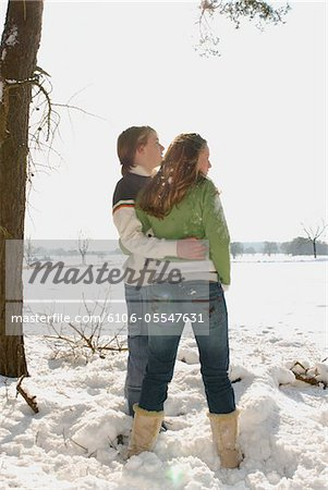 Teenage couple (14-16) standing in snow at edge of field Stock Photo - Premium Royalty-Free, Image code: 6106-05547631