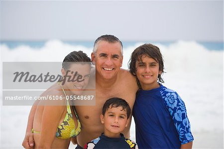Parents with children (6-13) on beach, smiling, portrait Stock Photo - Premium Royalty-Free, Image code: 6106-05548687