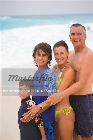 Parents with children (6-13) on beach, smiling, portrait Stock Photo - Premium Royalty-Free, Image code: 6106-05548688