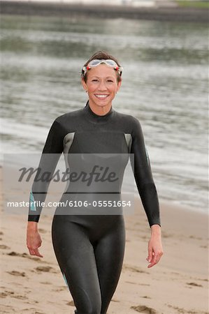 Smiling woman in wetsuit walking on the beach. Stock Photo - Premium Royalty-Free, Image code: 6106-05551654