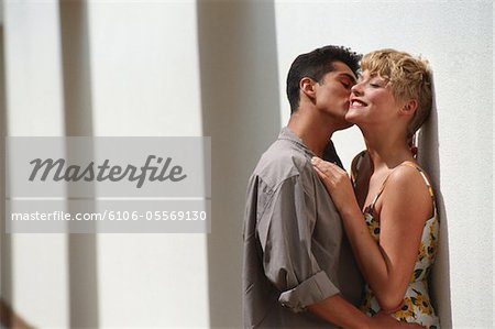 Young man kissing woman leaning against wall, close up