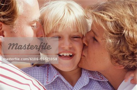 Two parents kissing daughter (6-7) on cheeks Stock Photo - Premium Royalty-Free, Image code: 6106-05571058