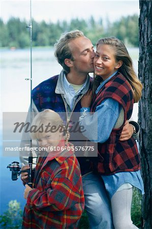 Parents with daughter (8-9) fishing at lake Stock Photo - Premium Royalty-Free, Image code: 6106-05576775