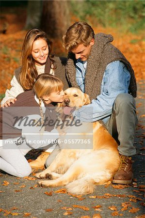 Parents with daughter (6-7) and dog on walk in forest Stock Photo - Premium Royalty-Free, Image code: 6106-05577365