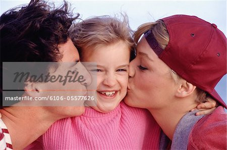 Parents kissing daughter (4-5) on cheeks, close-up Stock Photo - Premium Royalty-Free, Image code: 6106-05577626
