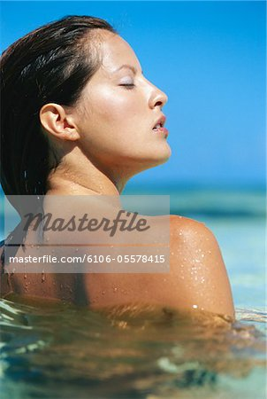Woman in water at beach Stock Photo - Premium Royalty-Free, Image code: 6106-05578415
