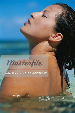 Woman in water at beach Stock Photo - Premium Royalty-Free, Image code: 6106-05578417
