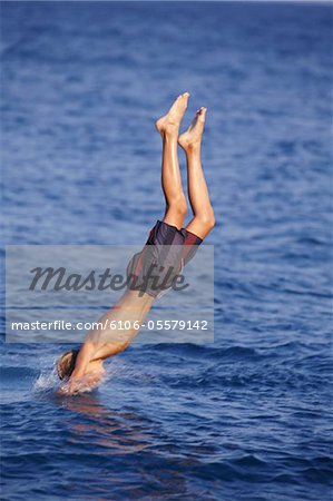 Boy diving in to sea Stock Photo - Premium Royalty-Free, Image code: 6106-05579142