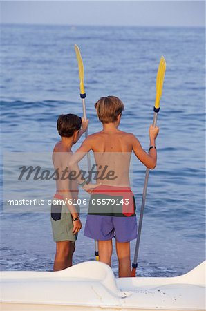 Two boys holding paddles, looking at sea, rear view Stock Photo - Premium Royalty-Free, Image code: 6106-05579143