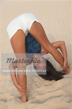Woman bending over, looking through legs at beach Stock Photo - Premium Royalty-Free, Image code: 6106-05583062