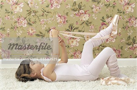 Girl (3-5) lying on back tying ballet shoes, side view Stock Photo - Premium Royalty-Free, Image code: 6106-05583525