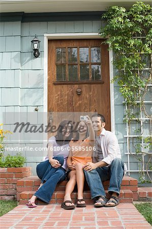 Mature couple and girl (11-13) photographing selves outside house door Stock Photo - Premium Royalty-Free, Image code: 6106-05585106