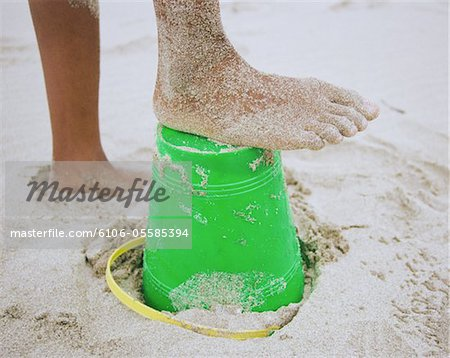 Girl (10-12) with sandy foot on plastic bucket at beach, low section Stock Photo - Premium Royalty-Free, Image code: 6106-05585394