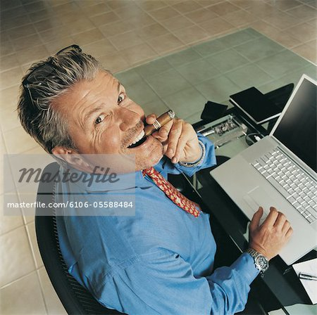 Portrait of a Ceo Smoking a Cigar at His Desk Stock Photo - Premium Royalty-Free, Image code: 6106-05588484