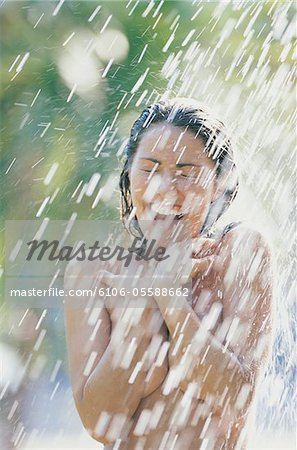 Naked Young Woman Having An Outdoor Shower in Summer Stock Photo - Premium Royalty-Free, Image code: 6106-05588662