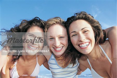 Portrait of Three, Smiling Women Standing on a Beach With their Arms Around Each Other Stock Photo - Premium Royalty-Free, Image code: 6106-05588667