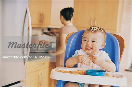 Messy Baby Sitting in a Highchair Eating Spaghetti and its Mother in the Background Stock Photo - Premium Royalty-Free, Image code: 6106-05589688