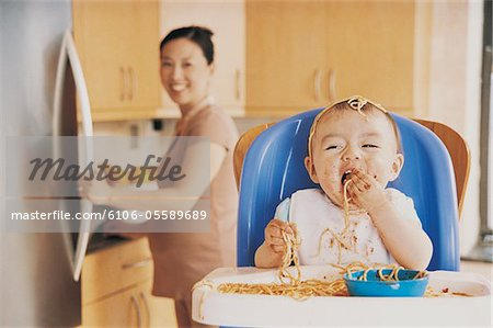 Messy Baby Eating Spaghetti Sitting in a Highchair and its Mother in the Background Stock Photo - Premium Royalty-Free, Image code: 6106-05589689