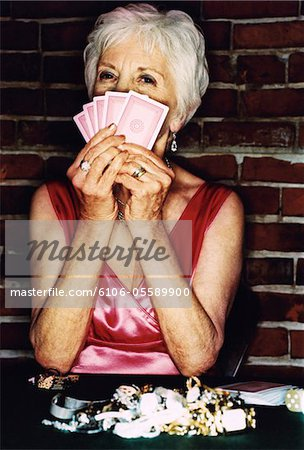 Senior Woman Sitting at a Table Gambling, Holding up Playing Cards in Front of her Face Stock Photo - Premium Royalty-Free, Image code: 6106-05589900