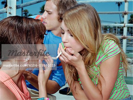 Two Teenage Girls Sit Face to Face Lighting Each Other's Cigarettes Stock Photo - Premium Royalty-Free, Image code: 6106-05590115
