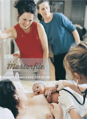 Mother Lying in a Hospital Bed, Holding a New Born Baby, With Friends Looking on and a Nurse Using a Stethoscope on the Child Stock Photo - Premium Royalty-Free, Image code: 6106-05590268
