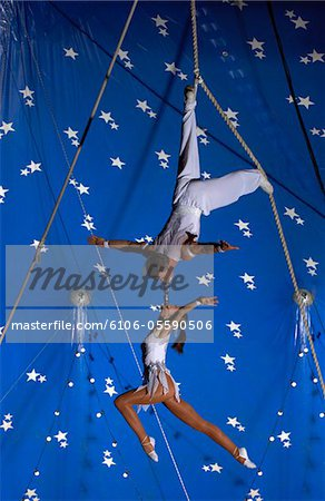 Female Trapeze Artist Hangs From a Male Trapeze Artist High Up in a Circus Tent, Connected to Him at the Mouth Stock Photo - Premium Royalty-Free, Image code: 6106-05590506