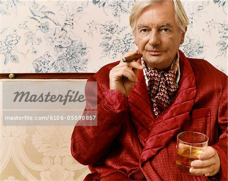 Portrait of an Aristocratic Man in a Smoking Jacket Sitting on a Chaise Longue Holding a Glass of Whiskey and a Cigar Stock Photo - Premium Royalty-Free, Image code: 6106-05590857
