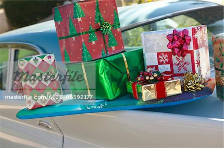 Pile of Wrapped Christmas Presents Balancing on the Back of a Classic Car Stock Photo - Premium Royalty-Free, Image code: 6106-05592177